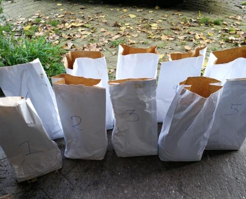 papieren-zakken-straatklinkers-blaadjes-gras